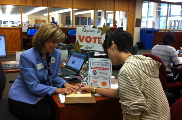 Amy Schlumpf Manion, Aurora University's Deputy Registrar for Voting, helps register an AU student