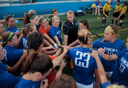 The women's soccer team, along with Head Coach Troy Edwards prepare for a game during their 2012 championship season