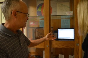 Rick Polad explains seismograph to Aurora University student