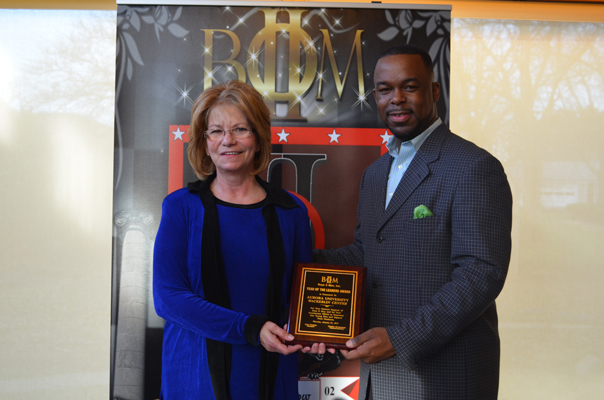 Barb Calvert, Director of Programming for the Wackerlin Center, accepts the Year of the Leaders Award award from Clayton Muhammad, Founder of Boys II Men.