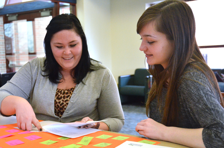 Seniors Grace Smith (left) and Ashley Finley prepare for the 11th Annual Undergraduate Research Conference at Aurora University.